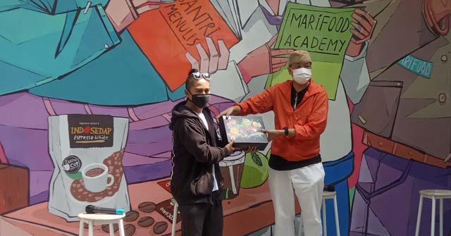 CEO Marimas Harjanto Halim menerima secara simbolis karya kolaborasi dari Arif Hadinta founder HOGK Studio, berlatar mural karya Arif. ( Christian Heru)
